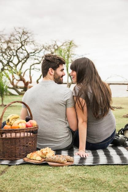 ピクニックバスケット、焼きたてのパン、若いカップルの前で、お互いを見て 無料写真
