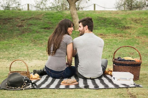 ピクニックにお互いを見て笑っている若いカップルのリアビュー 無料写真