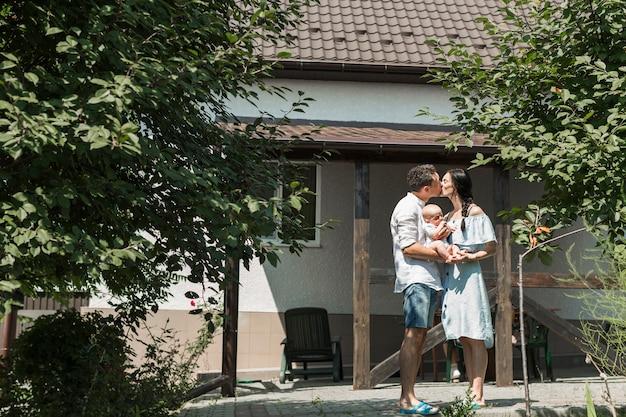 自宅の前でキスをしている赤ちゃんを運ぶカップル 無料写真