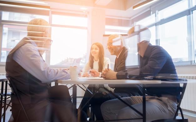 会議のテーブルの周りに座って笑顔のビジネスマンチーム 無料写真