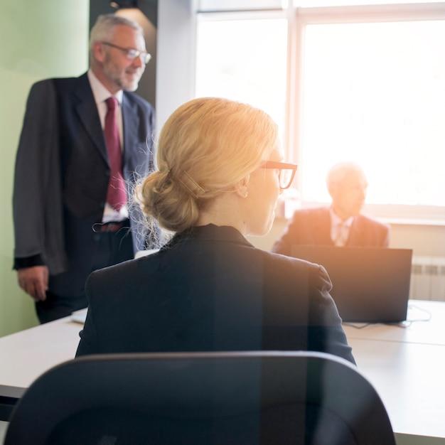 オフィスで彼女の同僚と金髪の若い実業家の後ろ姿 無料写真