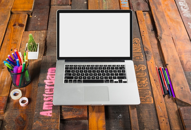 オフィスの木製机の上に文房具がある開いたラップトップ 無料写真