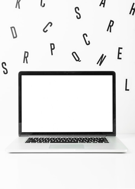 白い背景に散在したアルファベットの空白の画面のラップトップ 無料写真