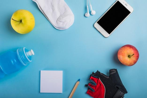 Яблоко; носок; наушники; бутылка с водой; клейкая нота; карандаш; перчатка и сотовый телефон на синем фоне Бесплатные Фотографии