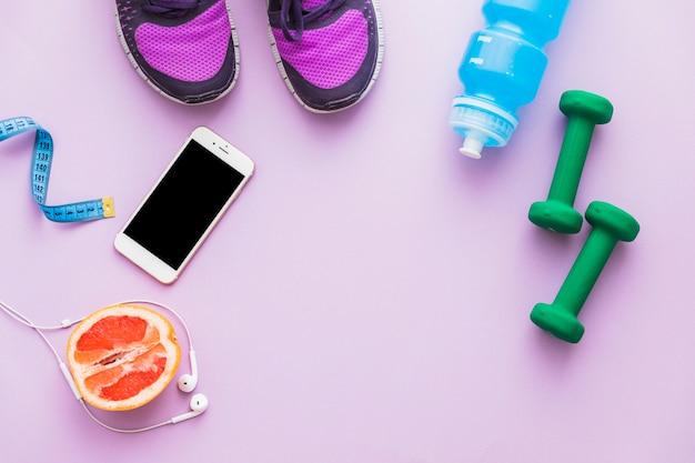 測定テープの上面図。ダンベル;靴;オレンジ色の果物を半分にする。水びん;ピンクの背景に携帯電話とイヤホン 無料写真
