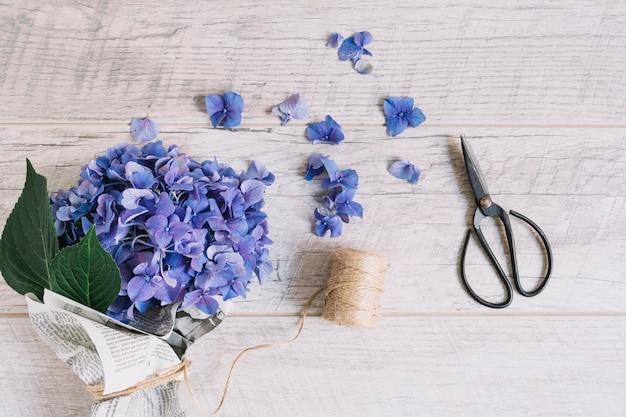 紫色の紫陽花の花束はスプールとはさみで結ばれた木製のテーブル 無料写真