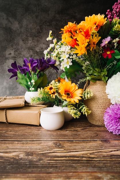 木製のテーブルにギフトボックスを持つ花瓶の多くのカラフルな花 無料写真