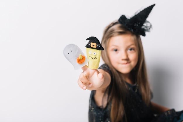 おもちゃと平和のジェスチャーを示す面白い魔女 無料写真
