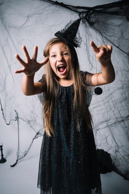 Маленькая ведьма, держащая паука и ревущую Бесплатные Фотографии