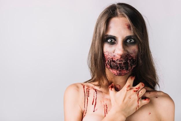 Жуткая женщина с поврежденным лицом, царапающим шею Бесплатные Фотографии