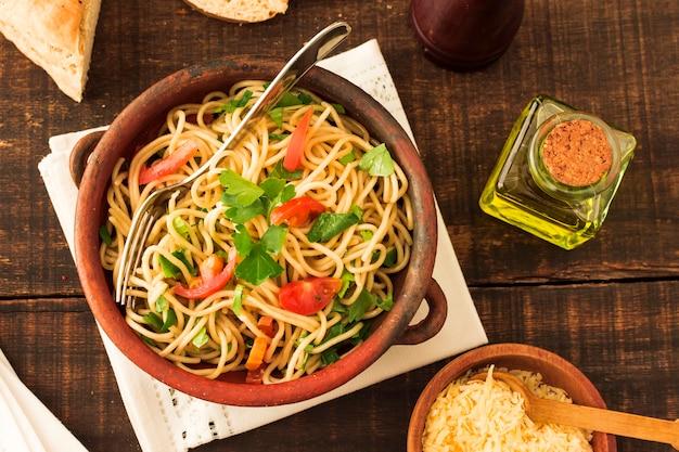 陶器のスパゲティパスタ上のトマトとコリアンダーのトッピング 無料写真