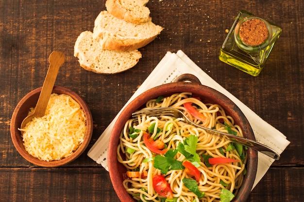 チーズ;木製の背景の上にパンとスパゲッティパスタ 無料写真