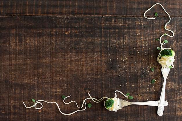 ブロッコリーと木製のテクスチャの背景に麺とフォーク 無料写真