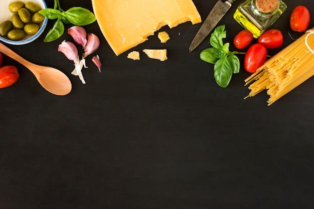 野菜と黒の背景にチーズとパスタ 無料写真