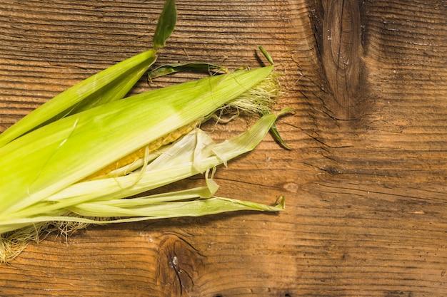 新鮮なトウモロコシ、木製の背景 無料写真