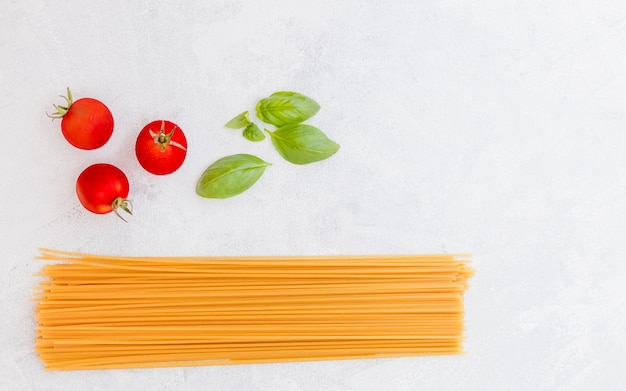 白いテクスチャの背景にトマトとバジルの生のスパゲッティの葉 無料写真