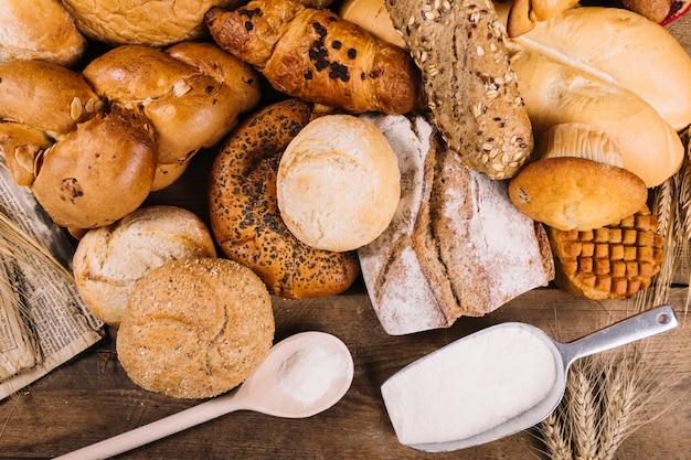 テーブル上の焼きたての穀物パンを使った小麦粉のオーバーヘッドビュー 無料写真