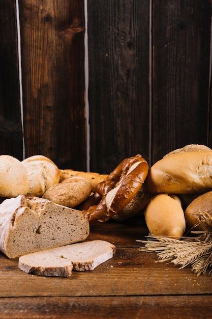 木製のテクスチャの背景に焼きたてのパン 無料写真