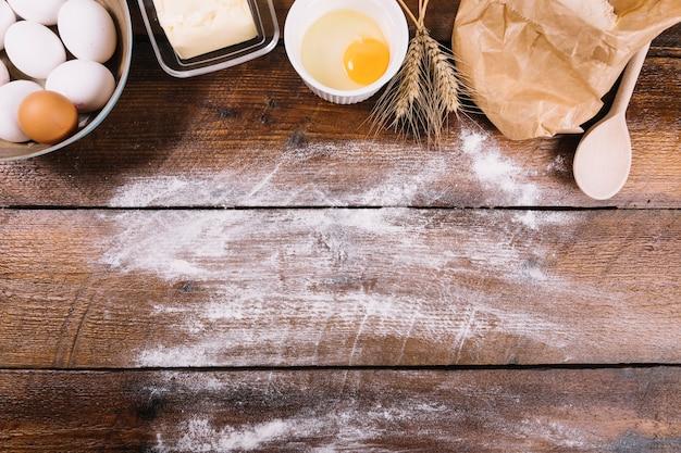 白い小麦粉の木製テーブル上の焼きたての材料 無料写真