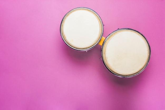 ピンクの背景にボンゴドラム 無料写真