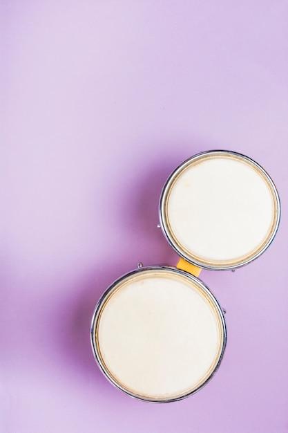 紫色の背景にボンゴドラムのオーバーヘッドビュー 無料写真