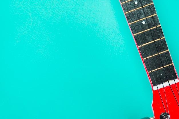 ターコイズブルーの背景に赤いアコースティッククラシックギターのクローズアップ 無料写真