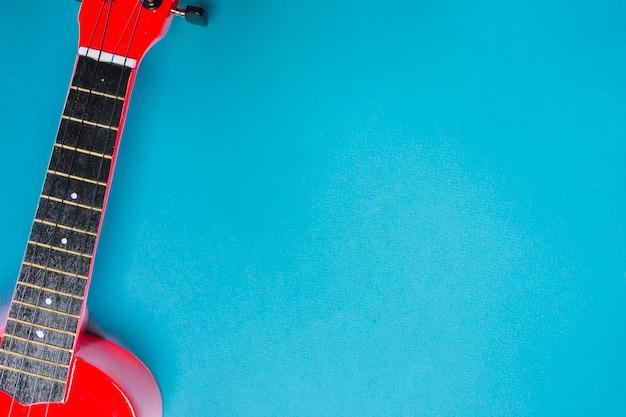 青色の背景に赤いアコースティック・クラシック・ギターのオーバーヘッド・ビュー 無料写真