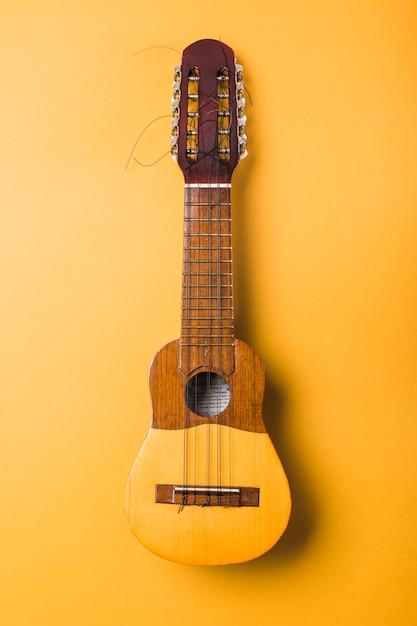 黄色の背景に壊れた弦を持つウクレレ 無料写真