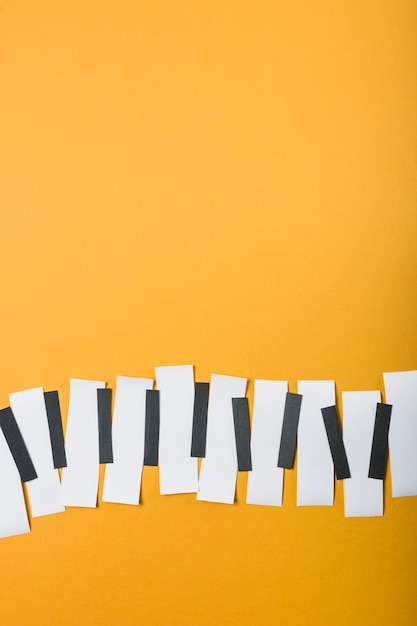 黄色の背景に白黒の紙で作られたピアノの鍵 無料写真