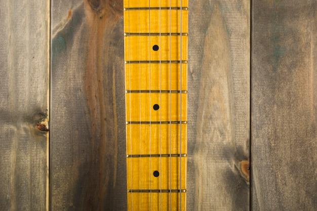 木製の背景にギターの弦とフレットボードのマクロショット 無料写真