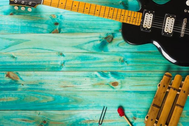 木製の木製テーブルの木琴と古典的なエレキギター 無料写真