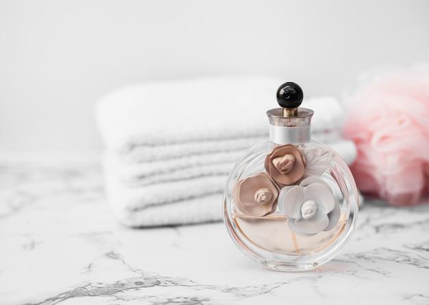 タオルと大理石の表面上のスポンジの前に香水瓶のクローズアップ 無料写真