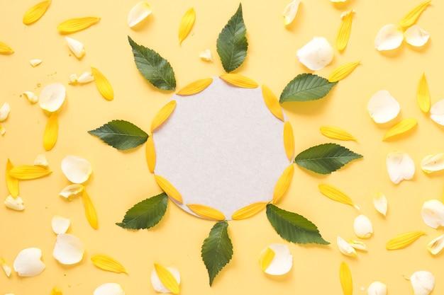 Круглая рамка, украшенная листьями и лепестками на желтом фоне Бесплатные Фотографии