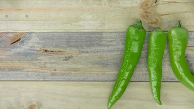 木製の背景に緑色の唐辛子の高い眺め 無料写真