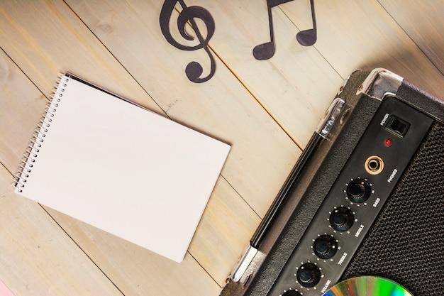 スパイラルメモ帳のオーバーヘッドビュー。木製の机の上に音符とアンプ 無料写真