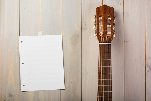 ギターの頭で木の壁に貼られた空白の音楽ページ 無料写真