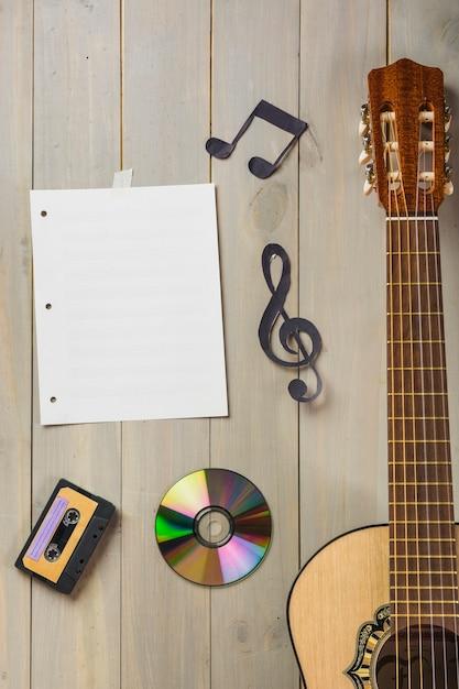 空の音楽ページ。カセットテープ;コンパクトディスク;ギターの木の壁に貼られた音符 無料写真