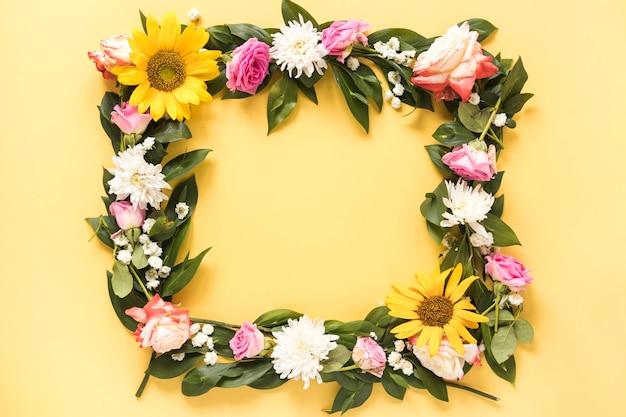 Повышенный вид красивых свежих цветов, образуя кадр на желтом фоне Бесплатные Фотографии