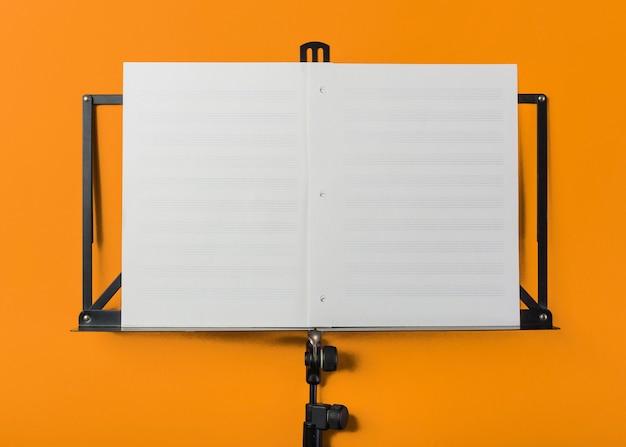 オレンジ色の背景に空白の白い音楽ページを持つ音楽スタンド 無料写真