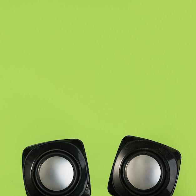 緑色の背景にワイヤレススピーカーのトップビュー 無料写真