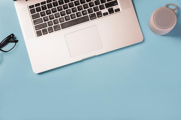 眼鏡のオーバーヘッドビュー。ブルーのスピーカーとラップトップの青い背景 無料写真