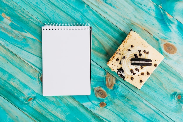 ペストリーとトルコ石の木製の背景に螺旋メモ帳 無料写真