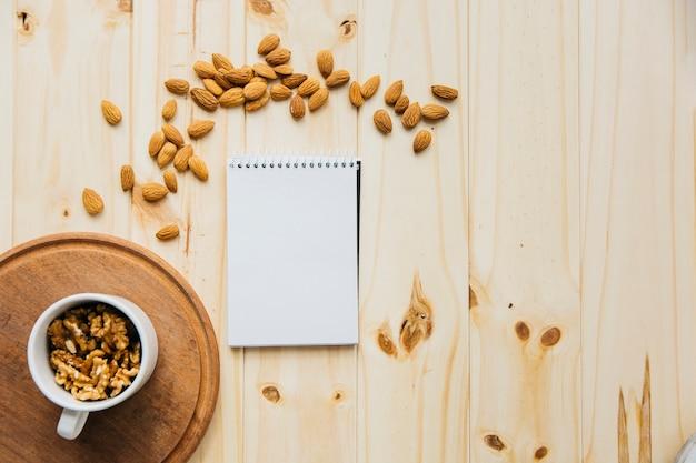 空白のメモ帳と木製の背景にアーモンドの近くにクルミのカップ 無料写真