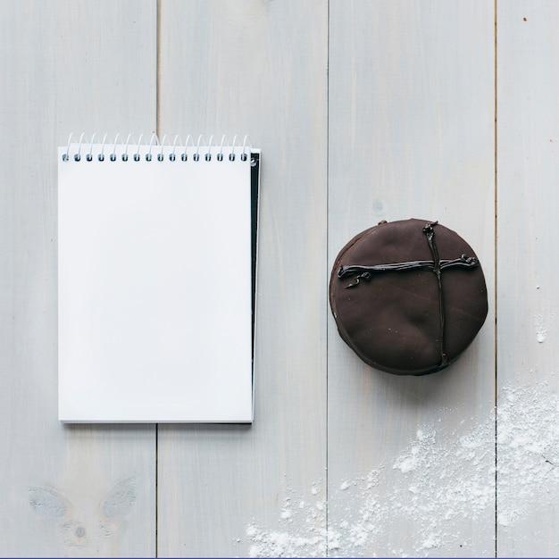 チョコレートマカロンと木製の厚板の空白のメモ帳の高い角度のビュー 無料写真
