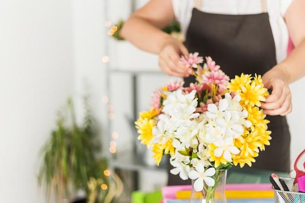 女性の花屋の前に新鮮な花のクローズアップ 無料写真