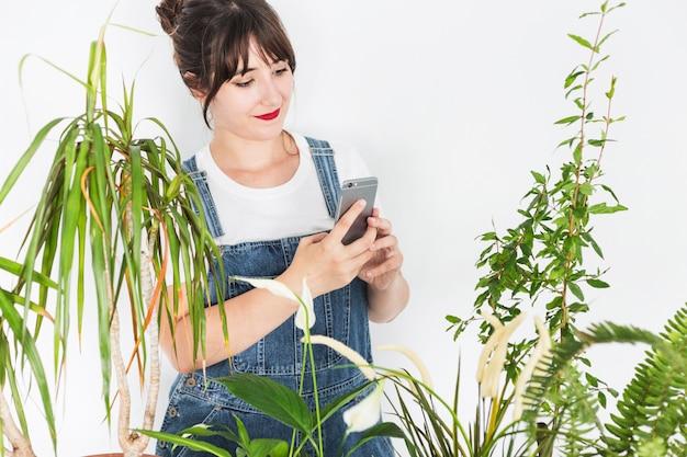 植物の近くで携帯電話を使用して女性の花屋 無料写真