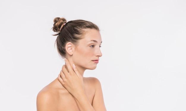 首に触れる裸の肩を持つかわいい女性 無料写真