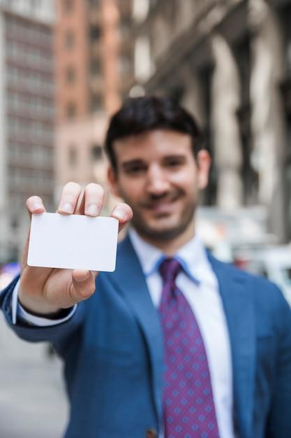 ビジターカードを示すぼんやりした実業家 無料写真