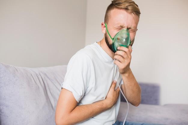 喘息ネブライザーを使用しているソファの男性 無料写真