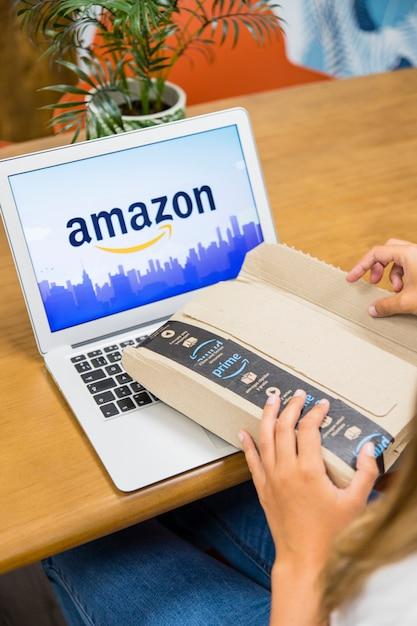 Женщина, сидящая с ноутбуком и открытие пакета доставки Бесплатные Фотографии
